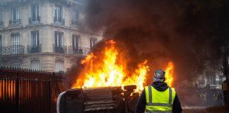 Un gilet jaune devant une voiture incendiée à Paris.