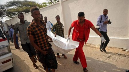 Quelques personnes portent le corps d'une victime de l'explosion de voiture près de l'hôtel Doorbin à Mogadiscio-le 24 février 2018