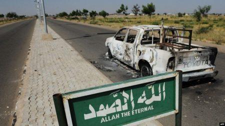 Une camionnette de patrouille de police brûlée reste abandonnée sur le bord d'une route déserte à Damaturu dans l'État de Yobe au Nigeria le 7 novembre