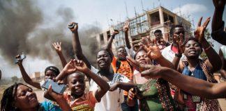 Les manifestants crient à côté d'un barrage routier au milieu de l'avenue principale de Beni lors d'une manifestation contre le report des élections sur le territoire des Beni et de la ville de Butembo le 27 décembre 2018.