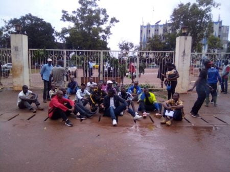 Les manifestants assis au sol devantt le portail du ministère de la jeunesse et des sports ainsi que du stade 20 000 places. Photo CNC / Jefferson Cyrille Yapendé