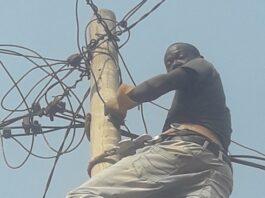 Un agent de l'Enerca installe la ligne d'un particulier à Bangui. Photo CNC