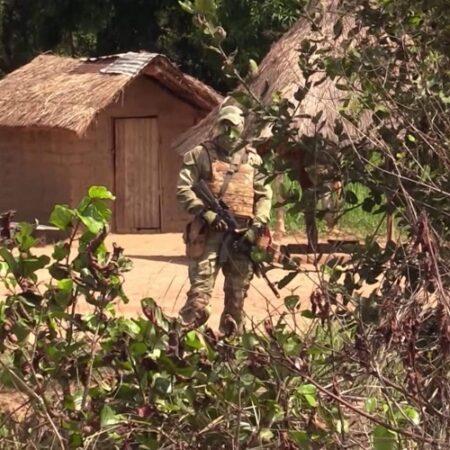 Un mercenaire russe devant des abris des villageois en fuite dans la brousse